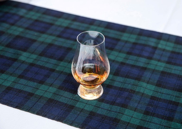 A glass of whisky on a blue and green tartan table cloth
